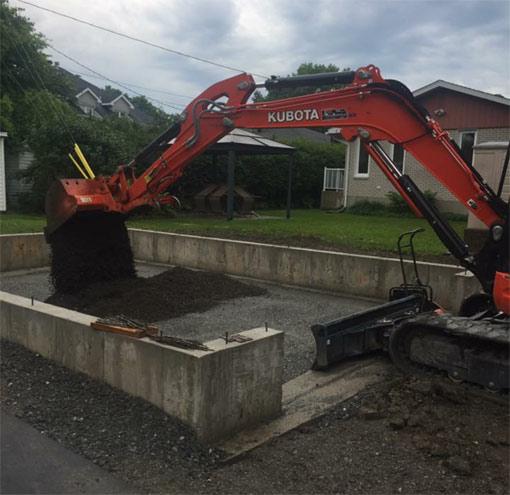 Photo d'une pelleteuse orange effectuant une excavation pour la réparation d'une fondation.